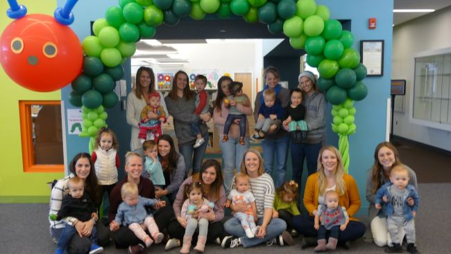 Women with babies inside the library sitting and standing in front of balloon display