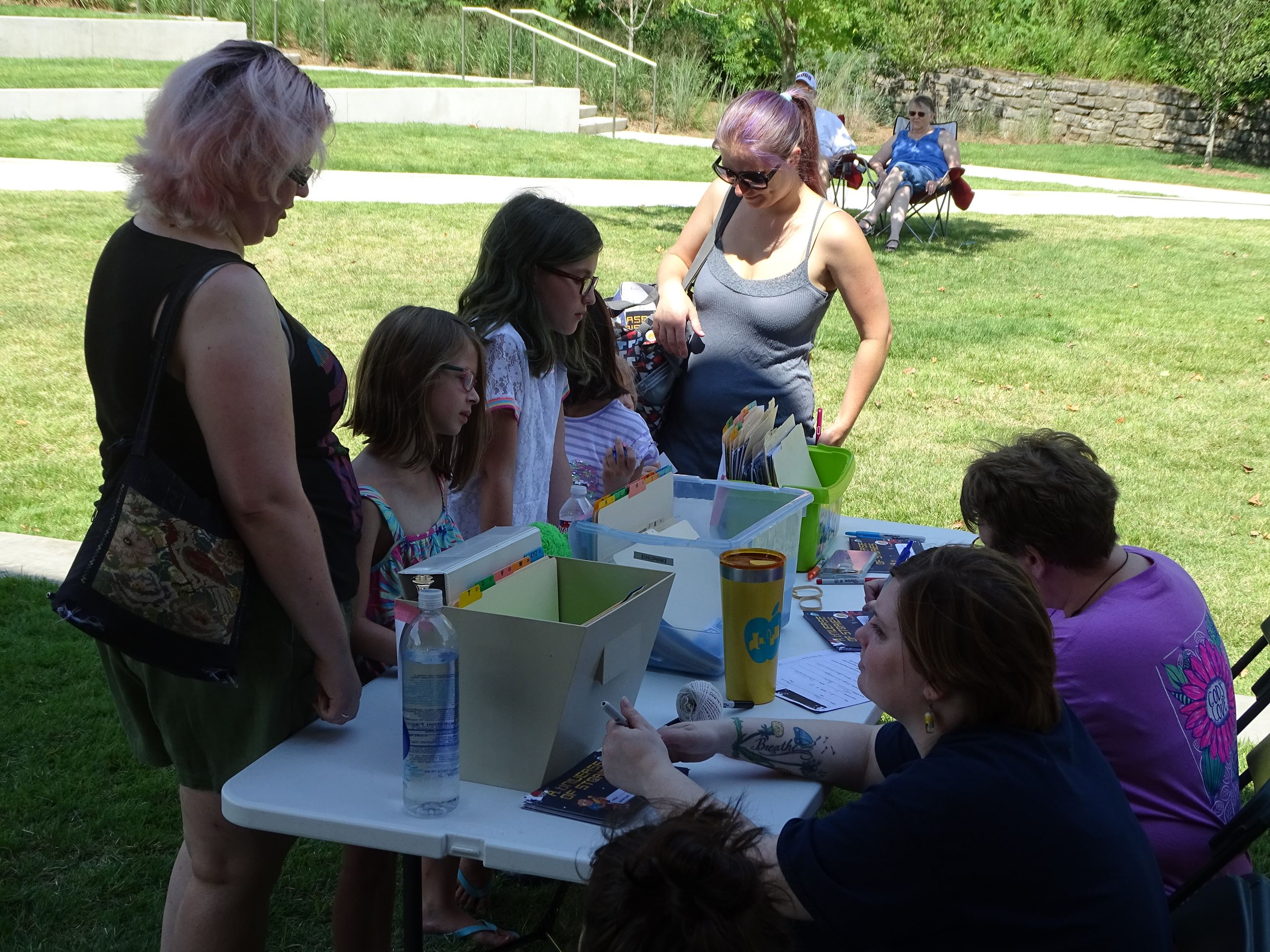 Children, parents and library staff at a table in Memorial Park registering for celebration