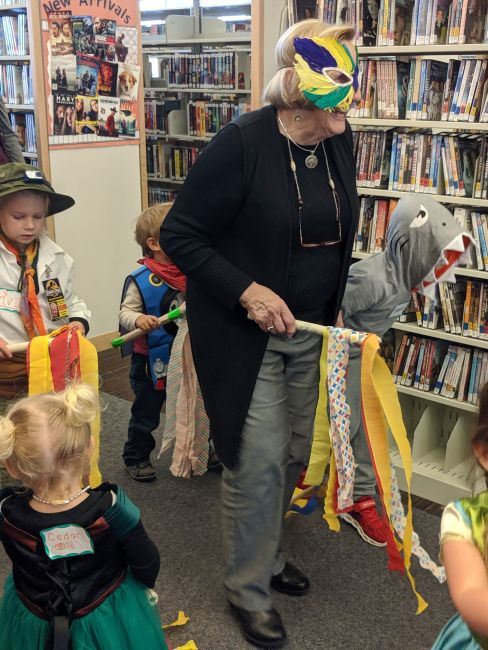 Children and Ms. Laura parading through the library in costumes