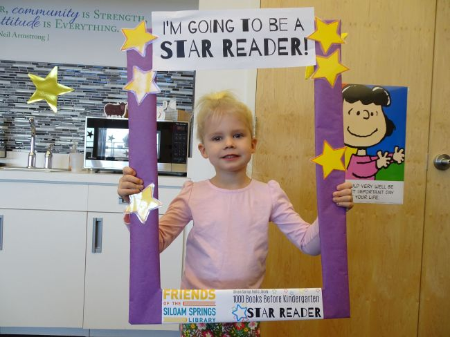 Girl holding a photo prop frame that says I'm going to be a star reader