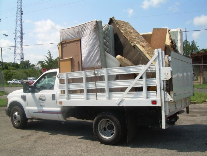 pickup truck bed loaded with old mattresses, furniture and other junk