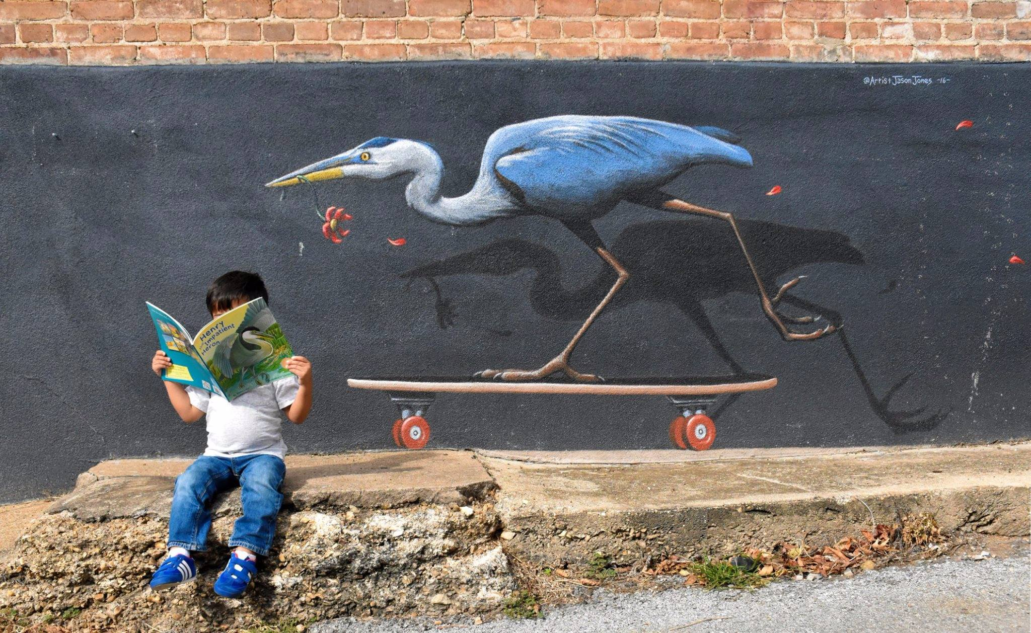 young boy sitting on concrete in front of a heron mural reading a book