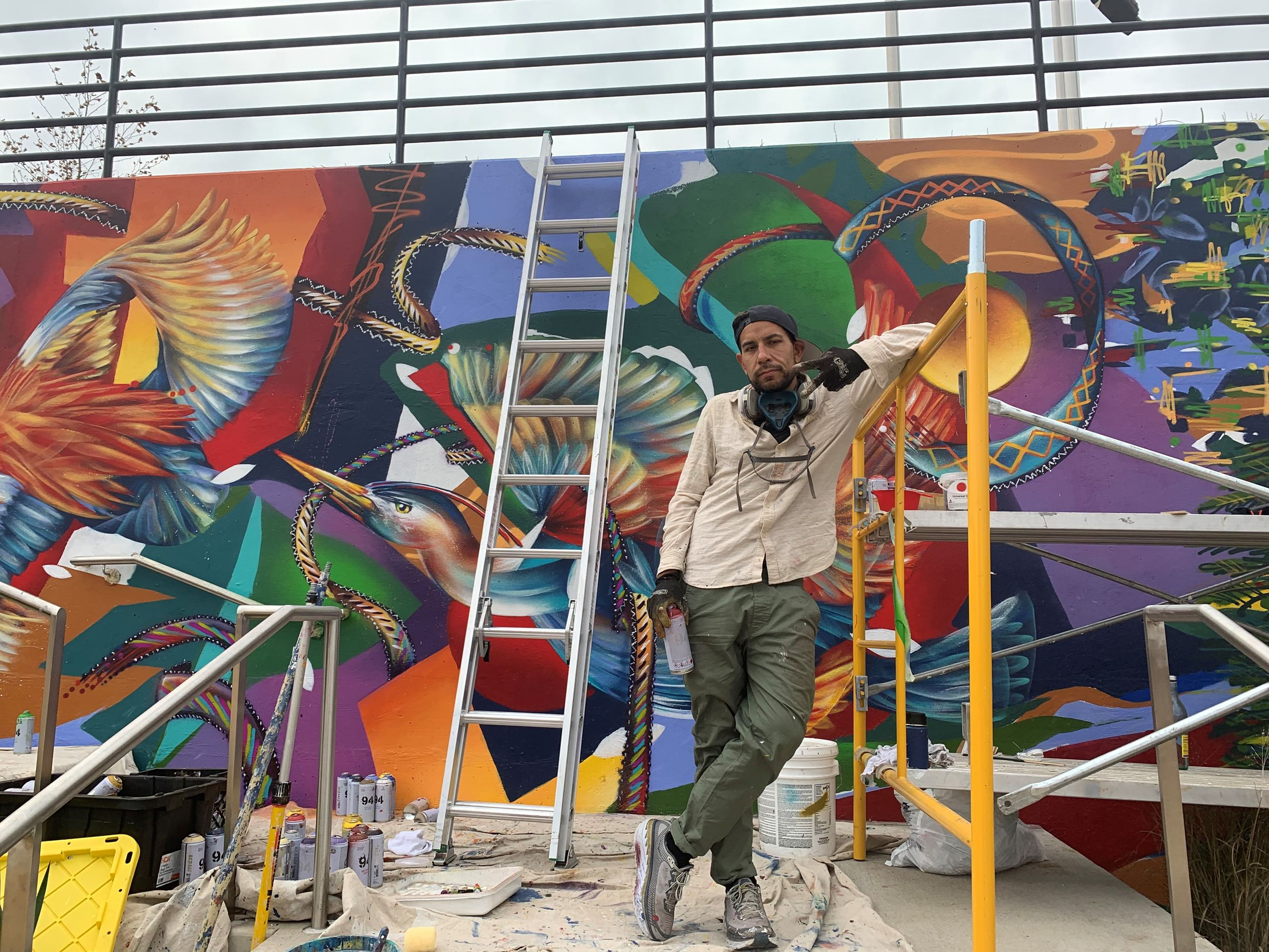Artists Yatika Fields in front of colorful mural of heron and fauna