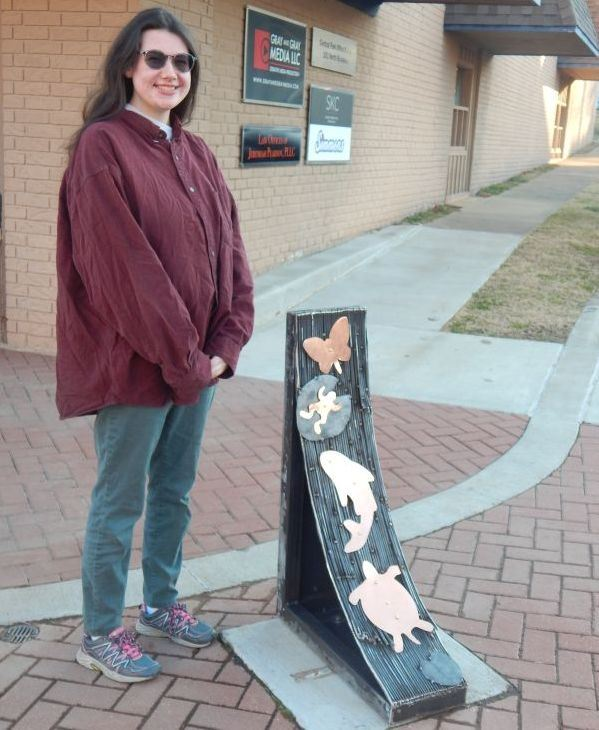 artist Piper standing in front of her metal sculpture in downtown Siloam Springs