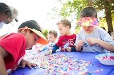 Children enjoying bead craft projects at Chalk It Up